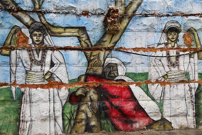 木にしがみついて土地から切り離されまいと抵抗する女性の壁画 / 東エルサレム