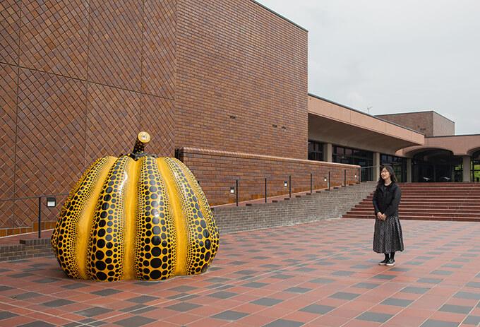 ゆるやかな階段で来館者を誘うスペース「エスプラナード」(スペイン語で広場の意味)にて、岩永悦子・福岡市美術館館長。前川建築の特徴である煉瓦色の磁器質タイルが美しい美術館のシンボル的な場所には、草間彌生が1994年に初めて手がけた野外彫刻作品《南瓜》が展示されている。 Photo : Seiji Tsuruoka