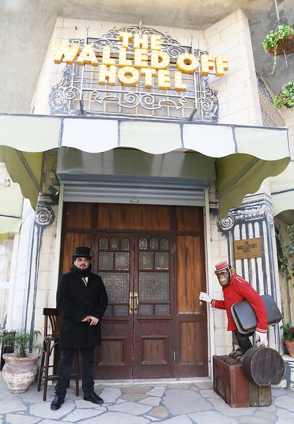 バンクシーが建てた、「The Walled Off Hotel(世界一眺めの悪いホテル)」。ホテルの入り口で出迎えるのは、トランクを抱えたチンパンジー / ベツレヘム