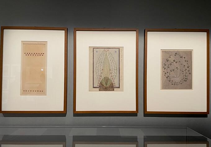ライフスタイルデザインのコーナーの展示風景。左よりエリエル・サーリネンの《テーブルクロスのスケッチ》1904年、《バラのタペストリーのスケッチ》1904年、《クッションのスケッチ》1905年 すべてフィンランド・デザイン・ミュージアム