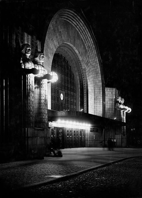 夜のヘルシンキ中央駅玄関、エーミル・ヴィークストロムによる彫像《ランタンを持つ人》Photo ©Museum of Finnish Architecture/ Foto Roos