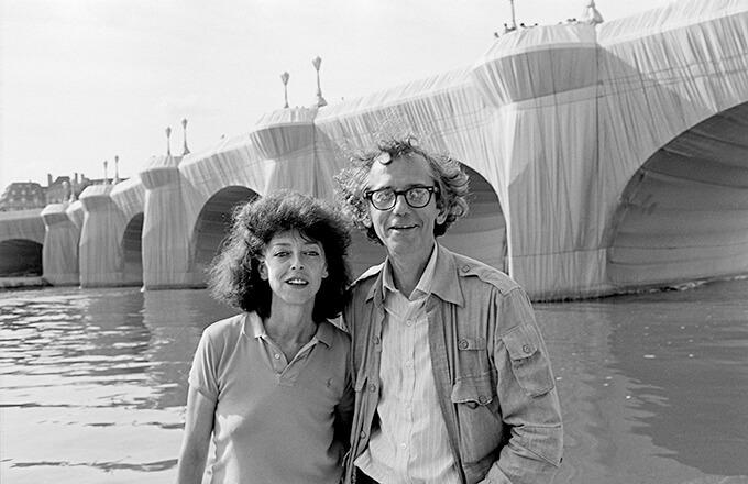 1985年、輝く黄金色に梱包されたポン・ヌフ橋(パリ)を背景にした、クリスト(右)とジャンヌクロード(左)Photo: Wolfgang Volz © 1985 Christo and Jeanne-Claude Foundation