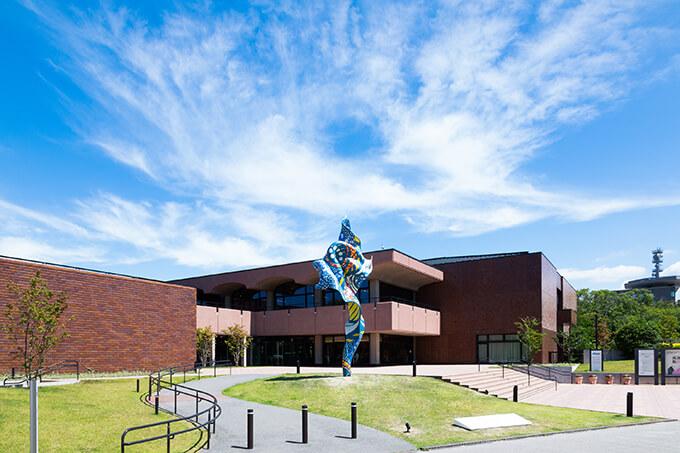 福岡市美術館の大濠公園側エントランス、インカ・ショニバレCBE《ウィンド・スカルプチャー(SG)Ⅱ》。2021年7月1日に公開された本作品は、色鮮やかな布が風に翻った瞬間を捉えた大型立体作品。本来柔らかく脆弱な布を賢固な彫刻作品としたショニバレの本シリーズについて岩永氏は、「不可能を可能にし、思い込みを打ち破る、ショニバレの思考を見事に体現している」(「インカ・ショニバレCBE: Flower Power」図録)と評する。Photo : Shintaro Yamanaka(Qsyum!)Copyright Yinka Shonibare CBE, 2021. Courtesy of James Cohan Gallery, New York