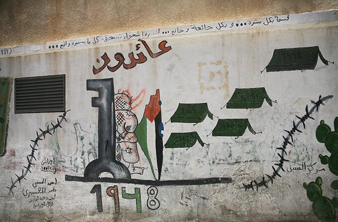 パレスチナ人の象徴、抵抗のシンボルであるハンダラが「帰還する」という文字とともに描かれる。テントに刻まれた数字はナクバ(大災厄)や第二次、第三次中東戦争、第一次、第二次インティファーダの年号。奪われた故郷の家の鍵を難民はいまも大切に受け継いでいることから、鍵も難民の象徴として描かれることが多い / デヘイシャ難民キャンプ